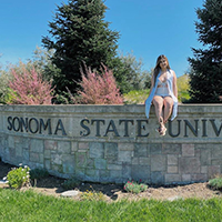 student sit on to of stone entry sign to Sonoma State University