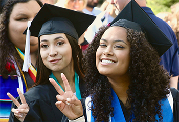 Two graduates in cap and gown smile and flash the peace sign